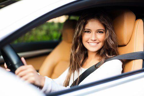 una ragazza sorridente al volante