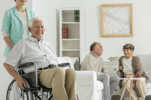 anziano su sedia a rotelle spinto da infermiera
