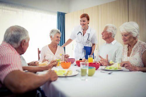 anziani a tavola con infermiera che si assicura che tutto vada bene