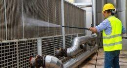 Un operaio tecnico indossa indumenti catarifrangenti e spruzza del liquido su una grata di metallo