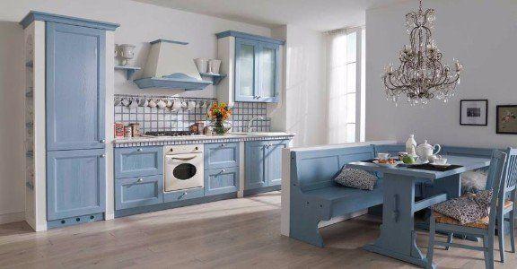 una cucina a blocco e un tavolo con una panca di color azzurro