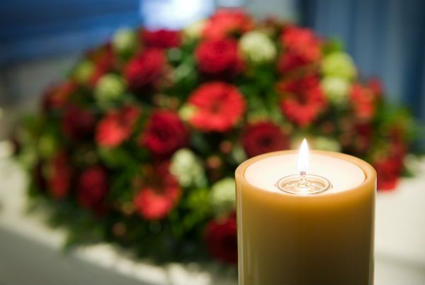 Cero votivo acceso e fiori rossi di sfondo
