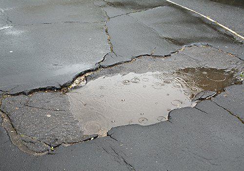 una strada danneggiata con una pozzanghera