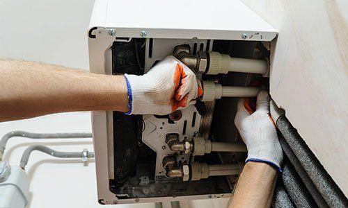 Idraulico che lavora coi tubi di una caldaia