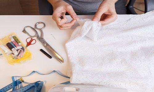 due mani con in mano una stoffa ricamata bianca