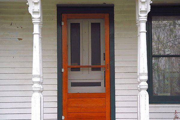 Zanzariera con infissi in legno di fronte a una porta