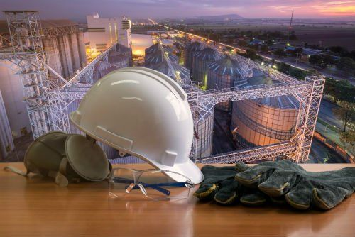 un elmetto,dei guanti, degli occhiali protettivi e dietro vista di alcuni stabili industriali