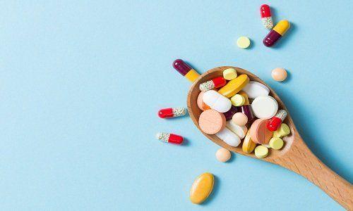 un cucchiaio di legno con pillole e pastiglie