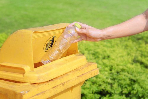 mano ricicla una bottiglia di plastica nel contenitore apposito