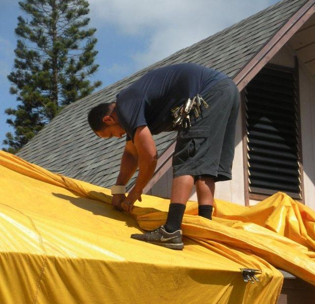 Worker setting up tent fumigation in Oahu