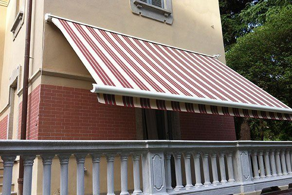 tenda che copre il balcone terrazze in colori bianco e arancio