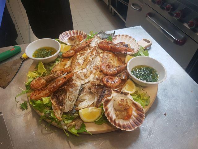 un piatto con un pesce alla griglia, patate e insalata mista