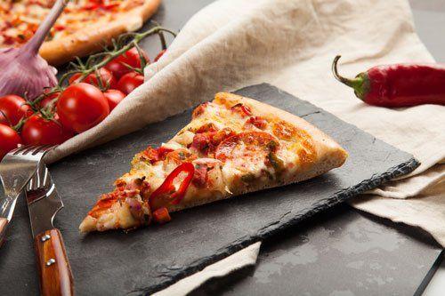 una fetta  di pizza, delle posate e un peperoncino