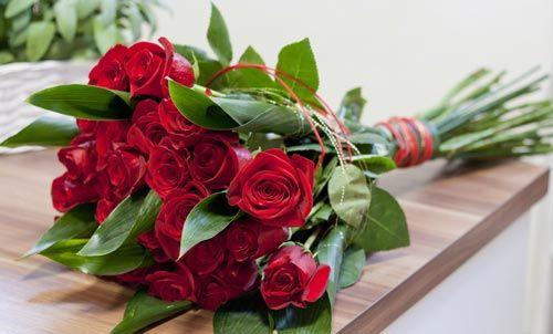 bouquet di rose rosse su sfondo legno