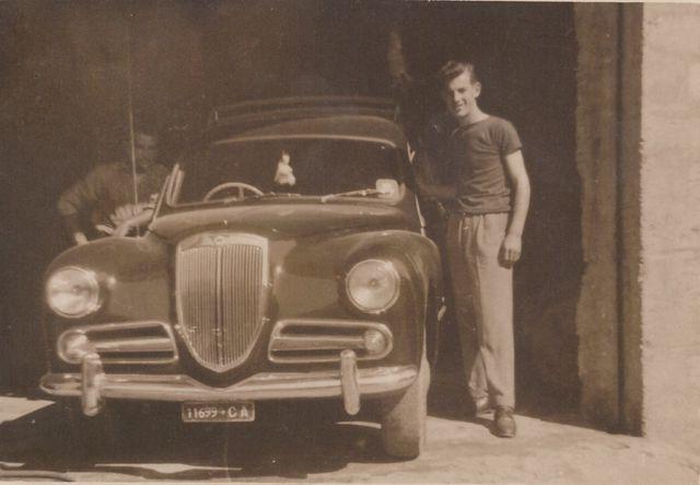 una foto in bianco e nero di un uomo vicino la macchina
