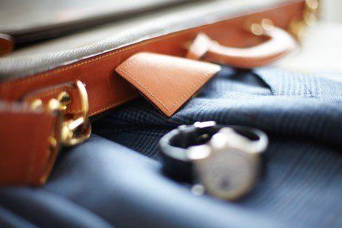 valigia con orologio e abito