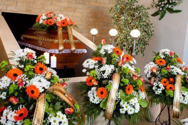 Bara coperta di fiori bianche e arance all'entrata della cripta,tre corone di fiori arance e bianche