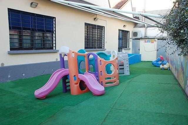 esterno di un asilo nido con uno scivolo e dei giochi per bambini