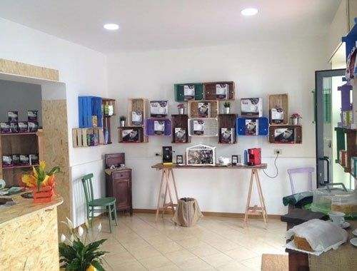 interno di un negozio con prodotti per caffe' dentro a delle mensole,un tavolo in legno e sulla sinistra un bancone