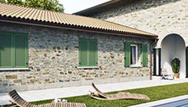 caseggiato con muri in pietra e persiane verdi
