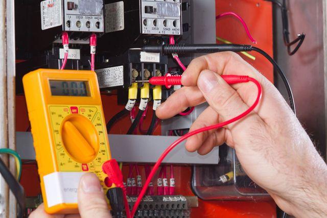 una mano con in mano un tester durante un controllo in un quadro elettrico