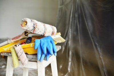 uno sgabello con sopra dei guanti da lavoro un rullo per dipingere e una vaschetta gialla per la vernice.