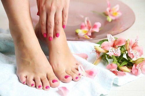 Mani e piedi con unghie rose e fiori accanto