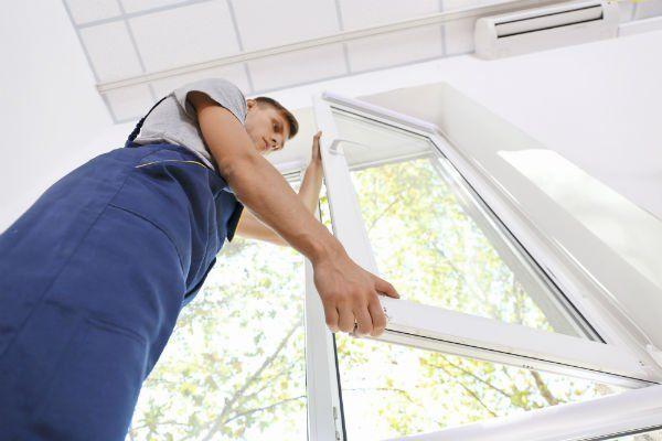 Operaio montando una finestra di PVC bianca