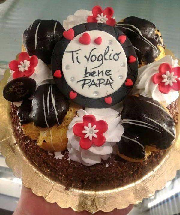 un torta con sopra dei bignè con una scritta Ti Voglio Bene Papà'