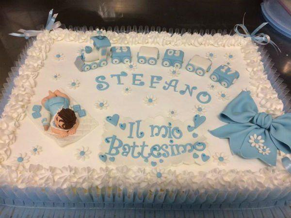 una torta per battesimo con sopra una forma di un trenino e un neonato