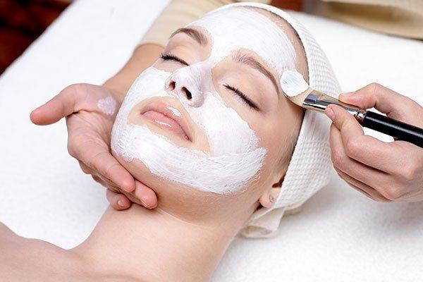 Un estetista che applica una maschera di bellezza su una donna sdraiata su un asciugamano bianco