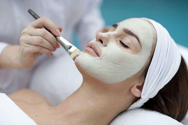 Una ragazza stesa su un lettino che si fa spalmare della crema di bellezza sul viso con un pennello