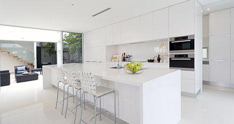 Una cucina a blocco di color bianco con una penisola grande con un lavandino e due sedie da bar