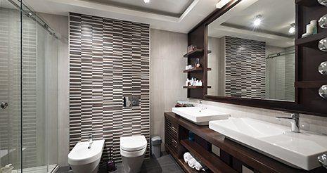 Un bagno ampio con un box doccia sulla destra, un WC. un bidet in mezzo e sulla destra un mobile con uno specchio