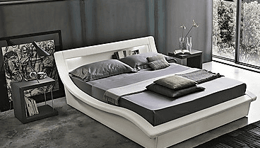 Una camera con un letto bianco, due comodini e uno sgabello con cuscino un imbottito di color viola