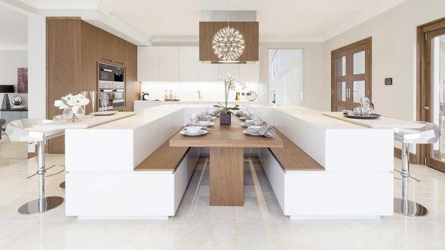 Una cucina componibile di color bianco con penisola in mezzo con un lavandino