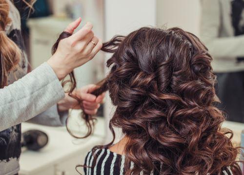 Parrucchiera realizza piega su capelli ricci