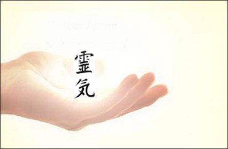 A Reiki symbol bathed in light above a cupped hand