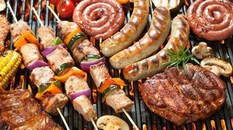 una griglia con sopra della carne e degli spiedini