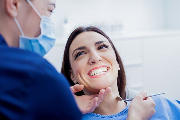 una donna che sorride mentre una dentista la visita