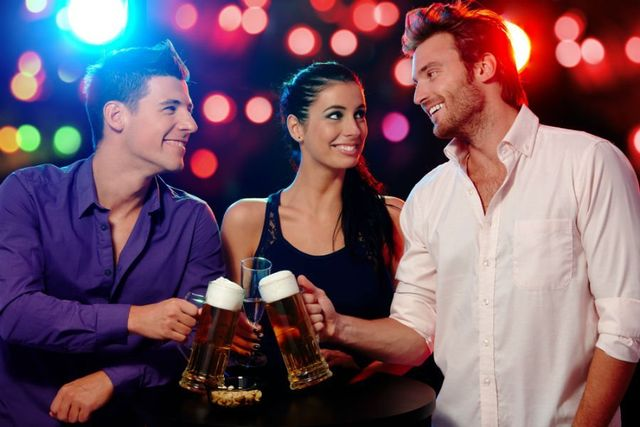 due ragazzi e una ragazza che sorridono con dei bicchieri di birra e vino in mano