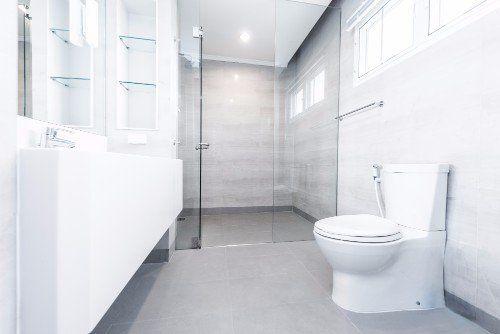 interno di un bagno con mobili bianchi e wc