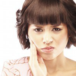 Woman With Look of Discomfort Holding Right Cheek