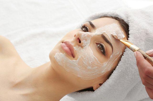 un' estetista usa un pennello mentre sta facendo una maschera facciale a una donna- Estetica Enza - Schio