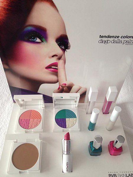 set di trucchi e smalti e dietro una rappresentazione su un cartellone di una donna truccata con diversi colori-estetica Enza-Schio