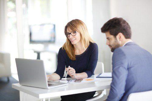 Un uomo ascoltando quello che una donna gli dice consultando il computer