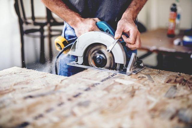uomo che taglia il legno