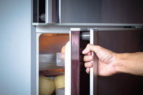 mano di uomo che apre un frigorifero