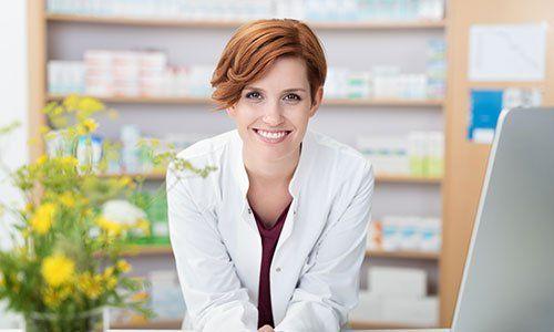 una donna con capelli corti castani con un camice bianco, accanto un vaso di fiori gialli e dietro uno scaffale in legno con delle medicine