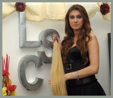 donna davanti all`insegna del negozio LSC tiene in mano una ciocca di extension bionde